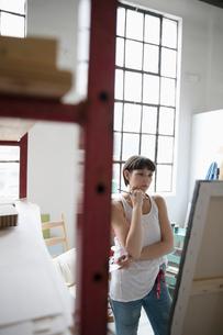 Serious, pensive female painter examining canvas painting in art studioの写真素材 [FYI02321419]
