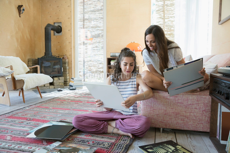 Female friends listening to music, looking at vinyl records in living roomの写真素材 [FYI02321422]