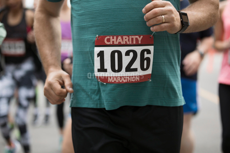 Close up male marathon runner wearing marathon bib, runningの写真素材 [FYI02321431]