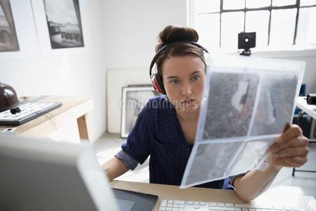 Female photographer with headphones examining photographic slides at laptop in art studioの写真素材 [FYI02321503]