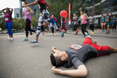 Exhausted male marathon runner collapsing at finish lineの写真素材 [FYI02321513]