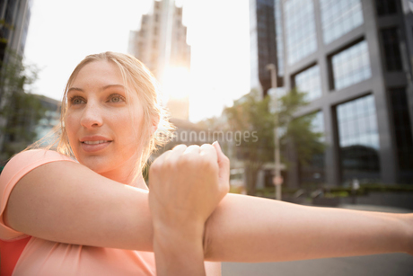 Young woman runner stretching arm on urban streetの写真素材 [FYI02321540]
