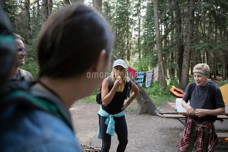Female outdoor school teacher blowing whistle at students at campsite in woodsの写真素材 [FYI02321542]