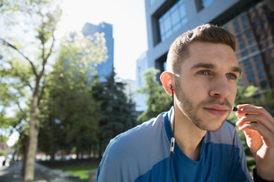 Serious young male runner holding earbud headphones, listening to music in urban parkの写真素材 [FYI02321563]
