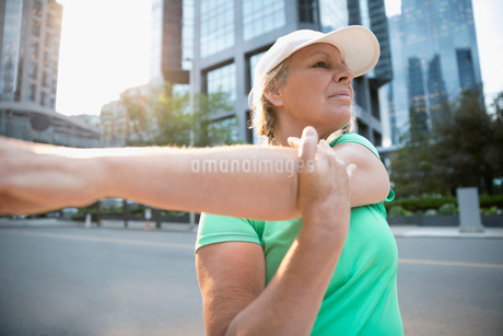 Mature female runner stretching arm on urban streetの写真素材 [FYI02321585]