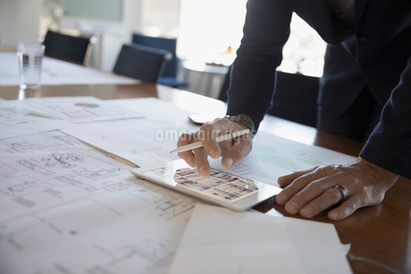 Businessman reviewing, editing paper and digital blueprints on digital tablet in conference roomの写真素材 [FYI02321599]