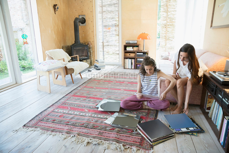 Female friends listening to music, looking at vinyl records in living roomの写真素材 [FYI02321674]