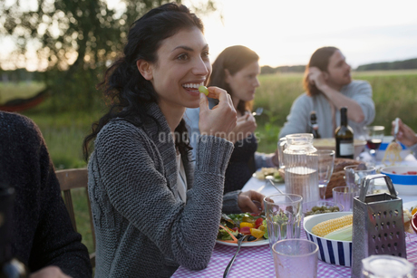 Smiling woman eating and enjoying garden party dinnerの写真素材 [FYI02321707]