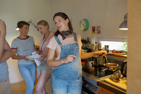 Pregnant woman cooking for friends in kitchenの写真素材 [FYI02321737]
