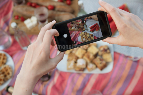 Personal perspective woman with camera phone photographing picnic foodの写真素材 [FYI02321739]