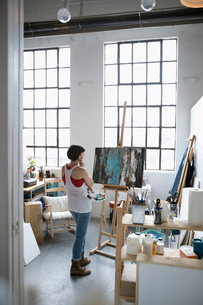 Female painter with palette examining canvas painting on easel in art studioの写真素材 [FYI02321741]