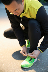 Male runner tying shoelaceの写真素材 [FYI02321768]