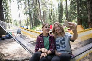 Teenage girl friends with smart phone taking selfie in hammock at outdoor school campsiteの写真素材 [FYI02321782]