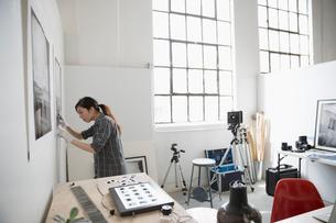 Female photographer examining large photograph print on wall in art studioの写真素材 [FYI02321802]