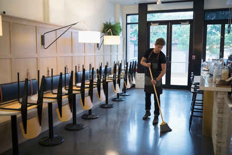 Male worker sweeping cafe with broomの写真素材 [FYI02321837]