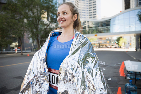 Smiling female marathon runner wrapped in thermal blanketの写真素材 [FYI02321847]