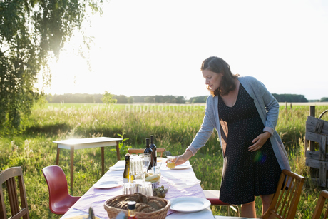 Pregnant woman setting the table for garden party dinner in sunny summer rural yardの写真素材 [FYI02321856]