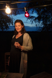 Portrait smiling pregnant woman under string lights on dark patioの写真素材 [FYI02321880]