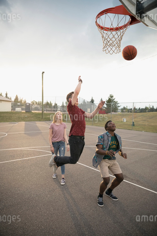 Teenage friends playing basketball on outdoor basketball courtの写真素材 [FYI02321919]