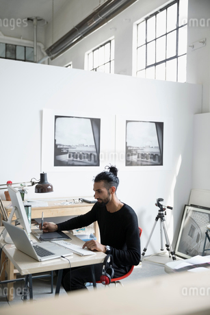 Male photographer using graphics tablet, designing at computer in art studioの写真素材 [FYI02321925]