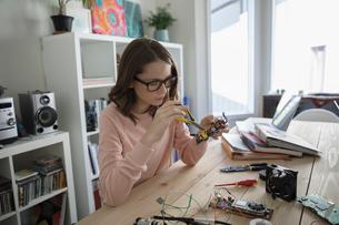 Teenage girl assembling electronics at tableの写真素材 [FYI02321933]