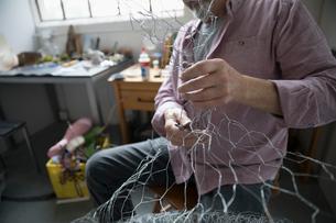 Male artist forming wire in art studioの写真素材 [FYI02321956]