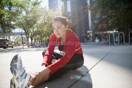 Woman stretching leg on sunny urban sidewalkの写真素材 [FYI02321958]
