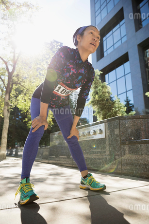 Tired mature female marathon runner resting with hands on knees on sunny urban sidewalkの写真素材 [FYI02322016]