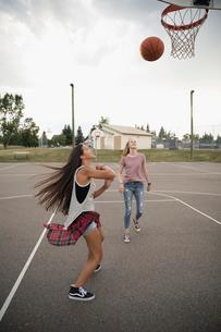Teenage girl friends playing basketball on outdoor basketball courtの写真素材 [FYI02322041]