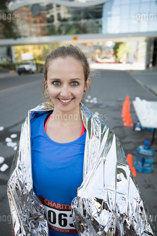 Portrait smiling female marathon runner wrapped in thermal blanketの写真素材 [FYI02322042]