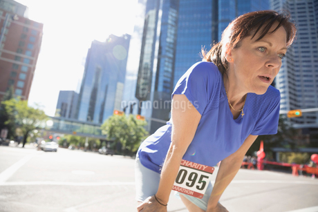 Tired mature female marathon runner resting with hands on knees on sunny urban streetの写真素材 [FYI02322067]