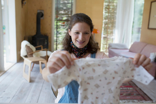 Pregnant woman looking at baby clothes in living roomの写真素材 [FYI02322071]