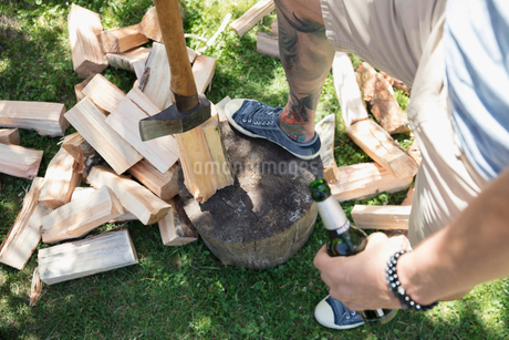 Man drinking beer and chopping wood on wood blockの写真素材 [FYI02322095]