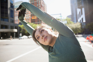 Female runner stretching on sunny urban streetの写真素材 [FYI02322104]