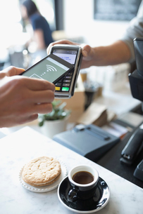 Customer paying with smart phone contactless payment at cafeの写真素材 [FYI02322110]