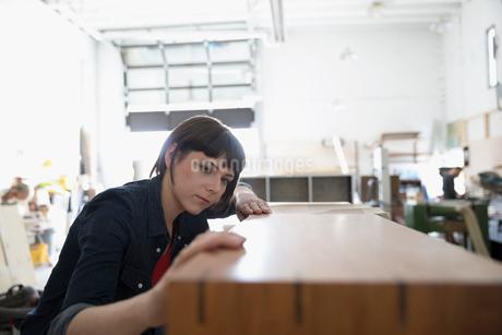 Focused female carpenter examining wood bench in workshopの写真素材 [FYI02322111]