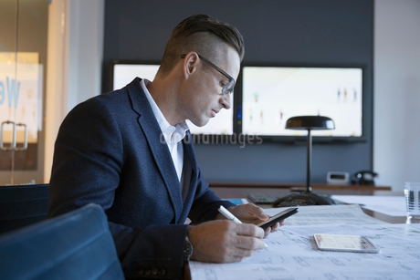 Businessman reviewing, editing paper and digital blueprints and using cell phone in conference roomの写真素材 [FYI02322116]