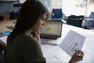 Female architect reviewing blueprints in conference roomの写真素材 [FYI02322119]