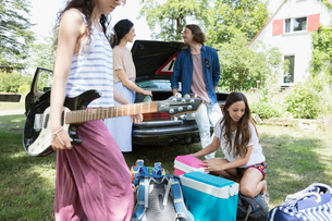 Friends arriving at summer house, unloading car and playing guitarの写真素材 [FYI02322127]