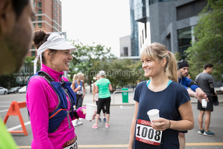 Smiling female marathon runners talking and drinking water on urban streetの写真素材 [FYI02322129]