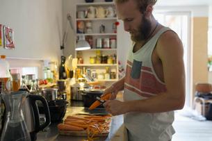 Man cooking, shredding carrots in kitchenの写真素材 [FYI02322214]