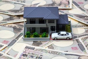一面の一万円札と家の模型と白い車の写真素材 [FYI02322521]