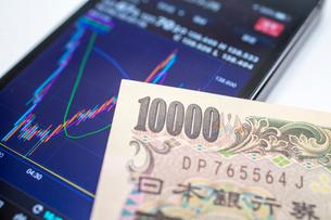 スマホのチャートと一万円札の写真素材 [FYI02322547]