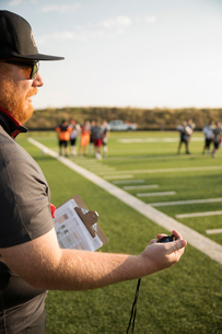 High school football coach with stopwatch timing practice on football fieldの写真素材 [FYI02322615]