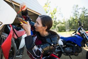 Woman fixing motorbike in drivewayの写真素材 [FYI02322769]