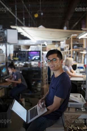 Portrait confident male engineer working at laptop in workshopの写真素材 [FYI02322840]