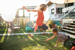 Brother and sister playing, jumping over wooden spoon in sunny backyardの写真素材 [FYI02322940]