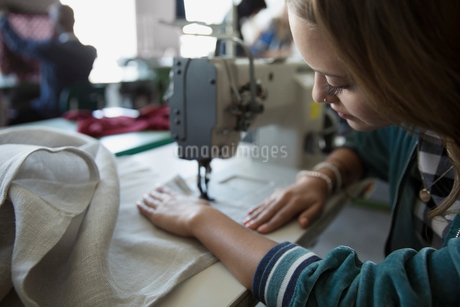 Female fashion design student using sewing machine in studioの写真素材 [FYI02322973]