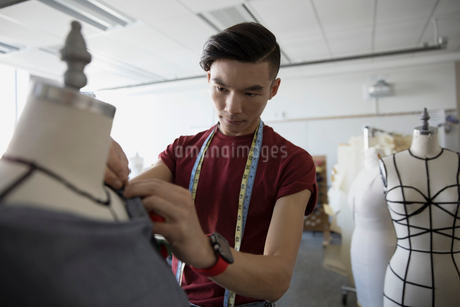 Male fashion design student pinning fabric on dressmakers model in studioの写真素材 [FYI02322979]