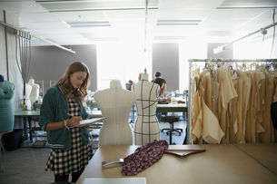 Female fashion design student sketching in notebook at dressmakers model in studioの写真素材 [FYI02323076]